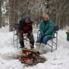 Taking a break from the action cooking smokies over a hot fire.